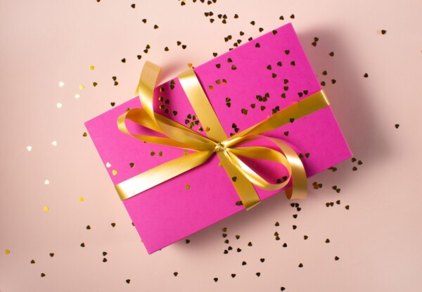 A bright pink gift box wrapped in gold ribbon is covered in shiny gold confetti.