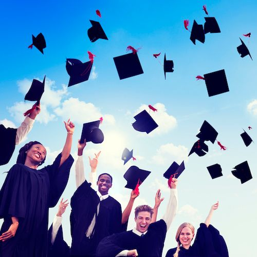 Graduating high school students throw their hats up in the air in celebration.