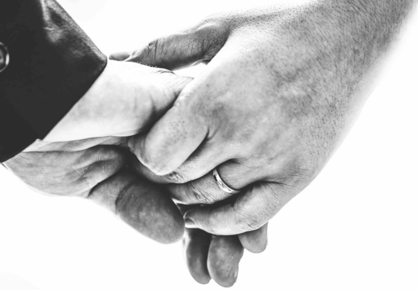 A close up on the interlinked hands of a married couple who is holding hands