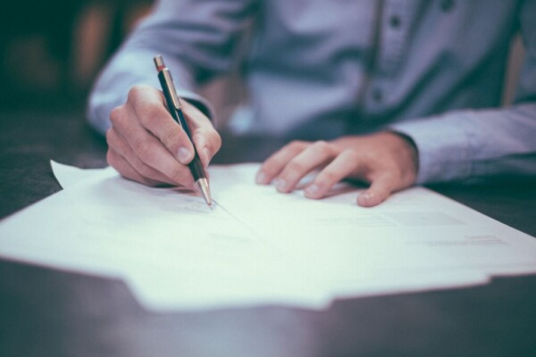A man wearing a grey dress shirt holds a pen and signs documents.