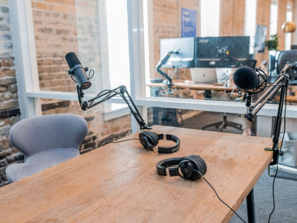 A grey chair sits behind a wooden table. On the table sit recording equipment including a black microphone and black headphones.